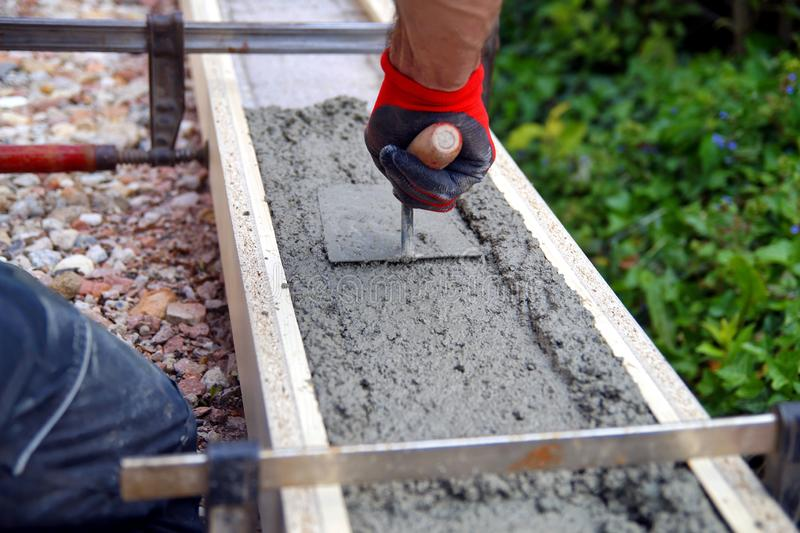 Foundation and form work. Leveling concrete with trowels, male worker hands spreading poured concrete. royalty free stock photo