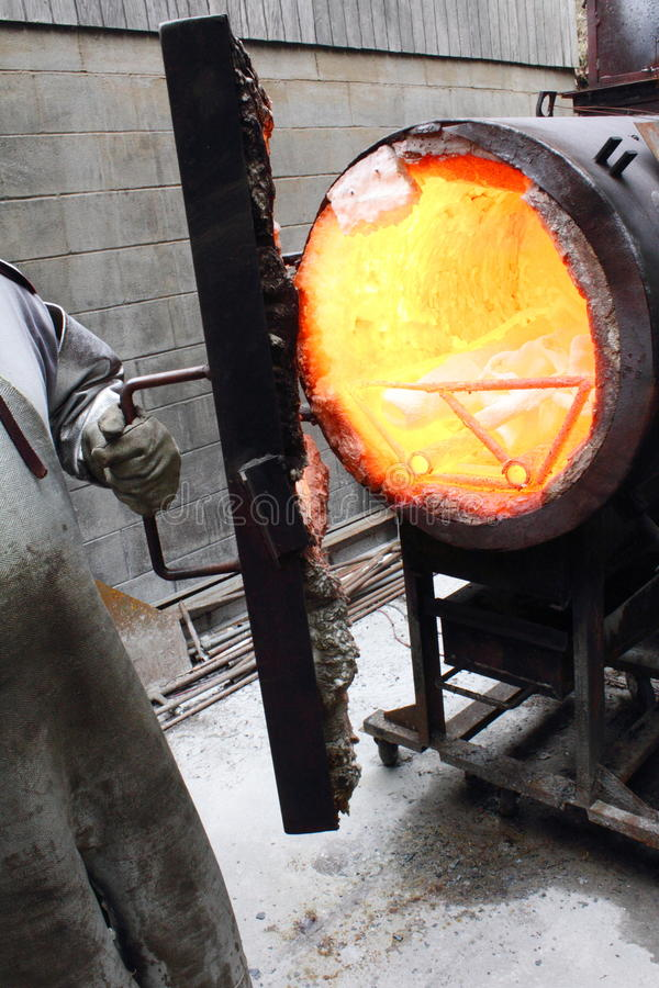Foundry Kiln for a Molten Metal Pour. Workmen's gloved hands wearing protective gear opening a foundry kiln to remove a mold for a molten metal pour. Red hot stock photos