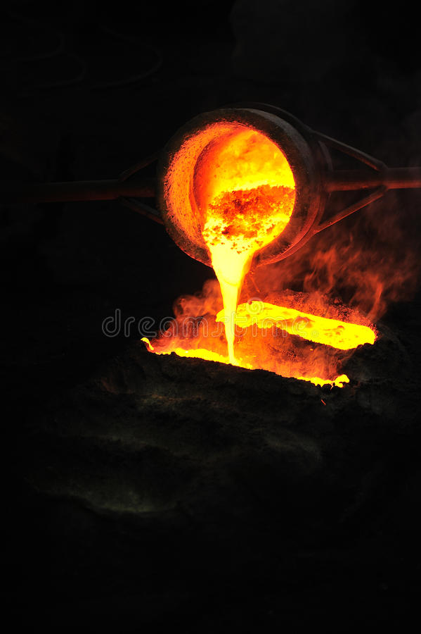 Foundry - molten metal poured from ladle into moul. D - emptying leftover royalty free stock photography