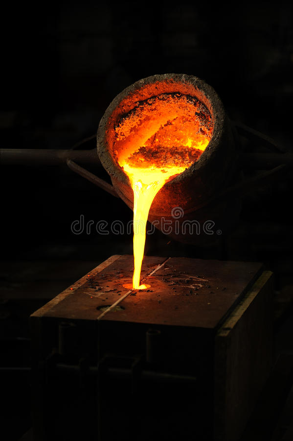 Foundry - molten metal poured from ladle into moul. D - lost wax casting stock photo