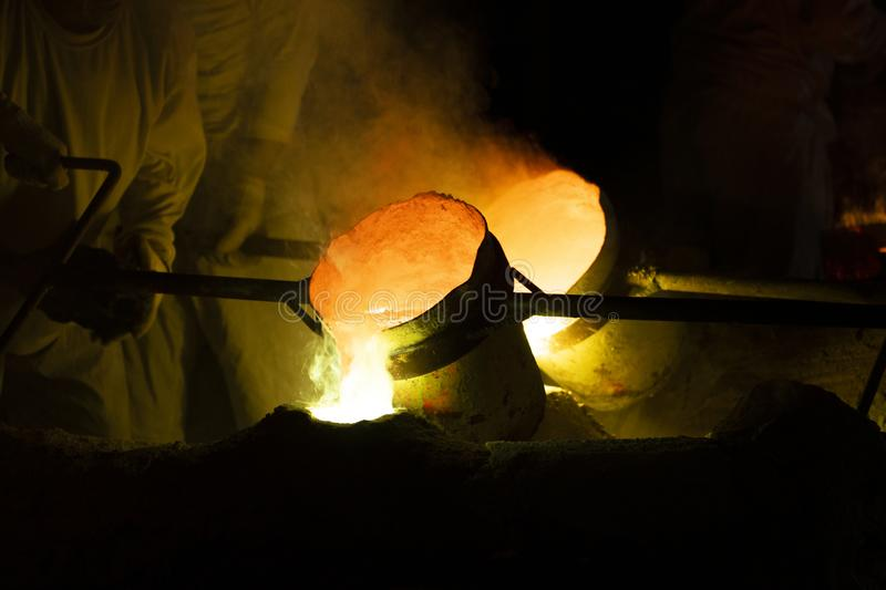 Foundry worker pouring hot molten metal into mold casting. Close up royalty free stock images