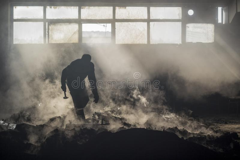 A foundry worker silhouette with his hammer royalty free stock images