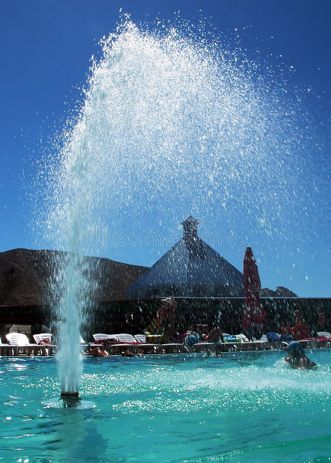 Fountain in Aqua Park. Water fountain in the swimming pool filled with fresh water which have turquoise color. There is person swimming by the right side of the royalty free stock images