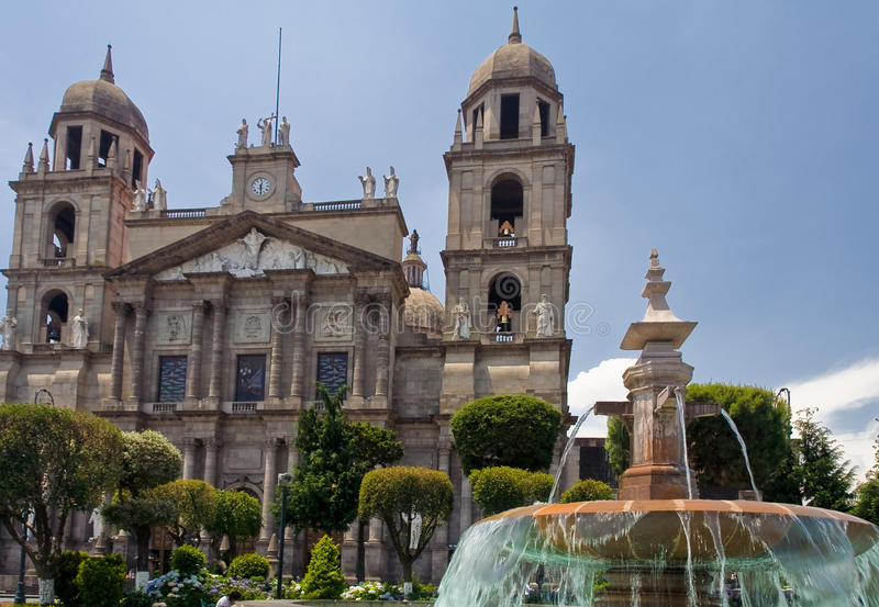 Fountain Cathedral Toluca de Lerdo Mexico. A fountain with blue water at the main plaza and the facade of the twin tower Cathedral of Toluca de Lerdo, Mexico stock photo