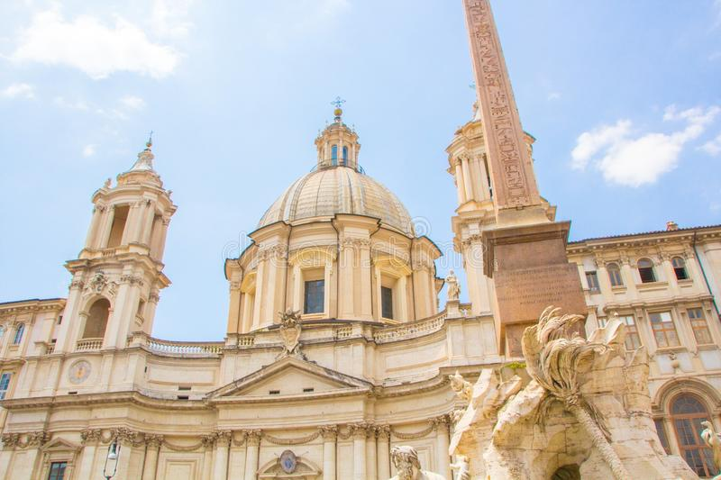 Fountain of the Four Rivers with an Egyptian obelisk and Sant Agnese Church on the famous Piazza Navona Square. Sunny summer day. Rome, Italy. Architecture and stock image
