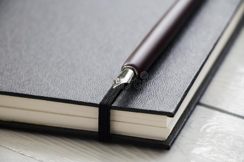 Book and nib pen. Fountain nib pen with black leather book put on wooden with space use for texts or products display royalty free stock images