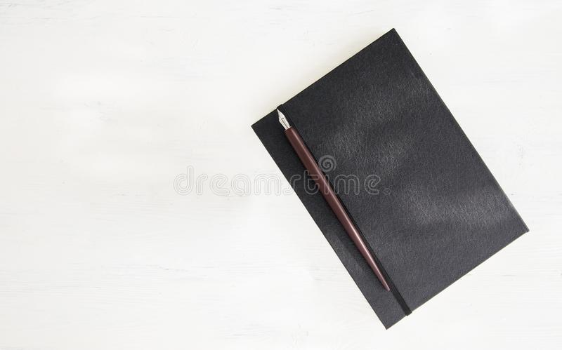 Book and nib pen. Fountain nib pen with black leather book put on wooden with space use for texts or products display stock photo