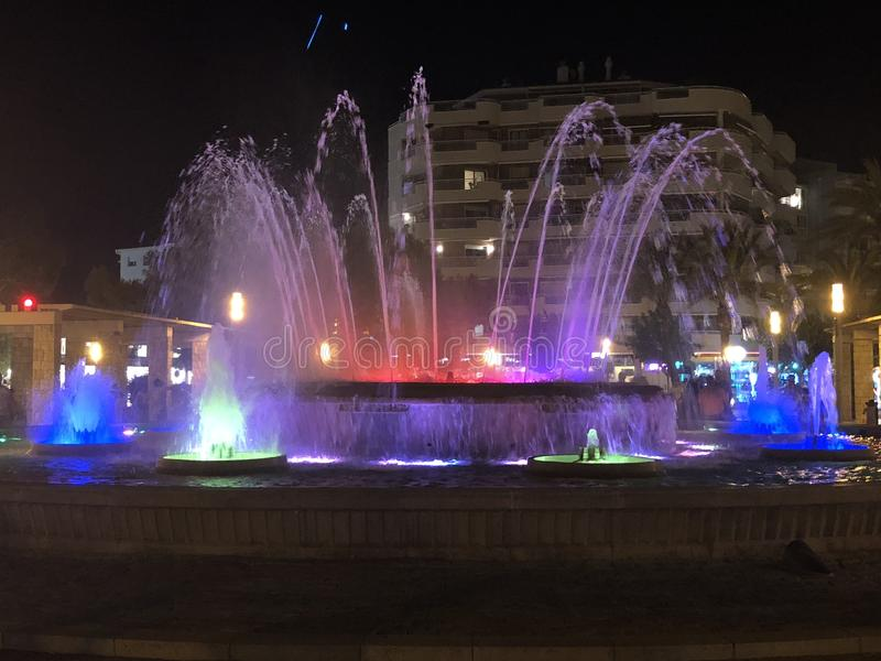 Fountain at night lighted with various colours royalty free stock photos