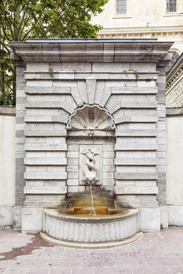 Fountain at the old town of Boulogne-sur-Mer, France. Ornate fountain with two-tailed fish at the fortified city of Boulogne-sur-Mer, Pas-de-Calais, France stock photo