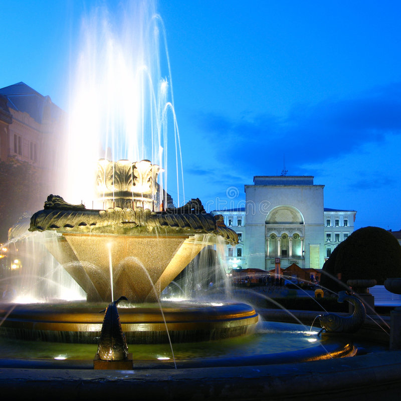 Fountain in Opera Square, Timisoara, Romania. Decorative fountain in Opera Square, with the Opera House in the background at twilight in Timisoara, Romania. The stock photography