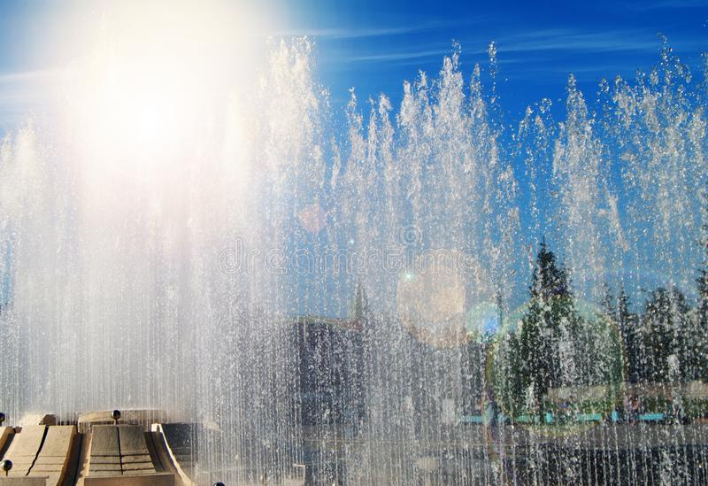 Fountain in the Park with water jets and splashes against the blue sky on a Sunny summer day royalty free stock photos