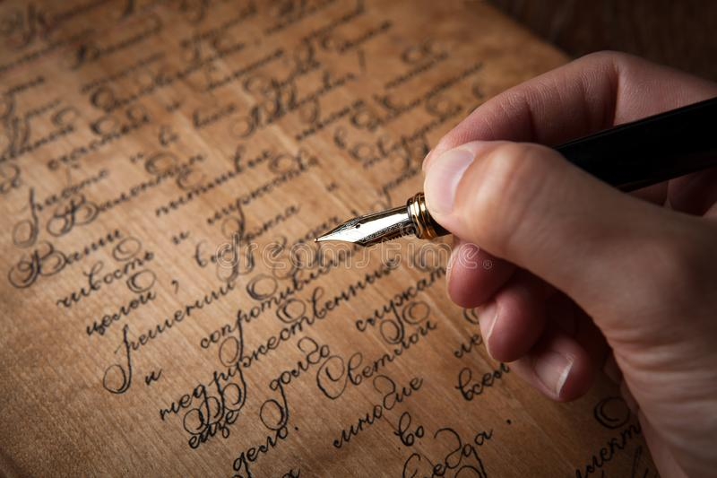 Fountain pen in the hand on letter with text stock images