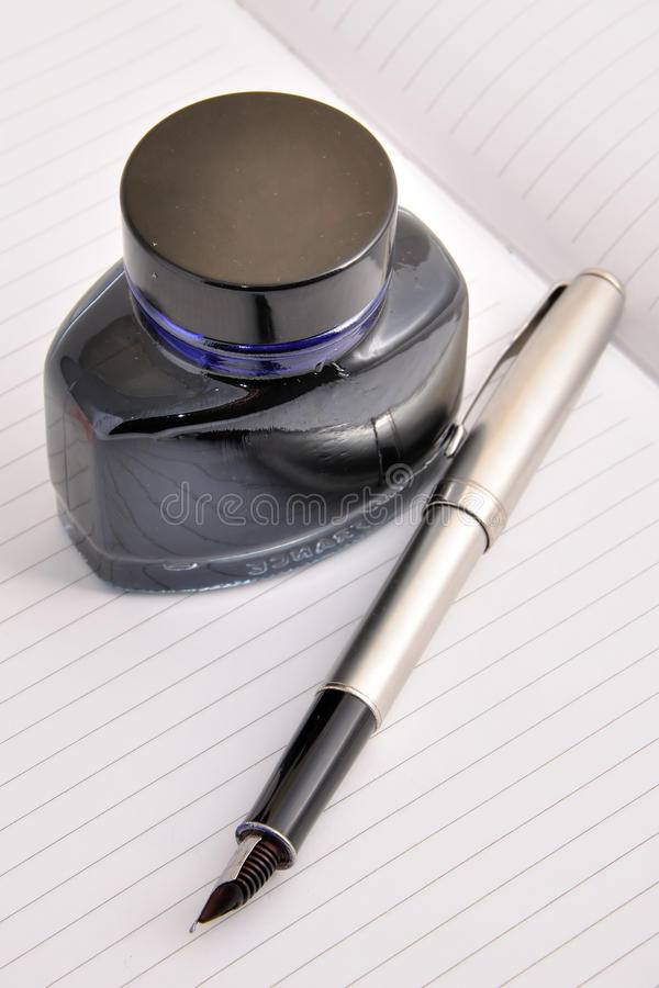 Fountain pen and ink bottle lying on a clean sheet. Of notebook stock photo