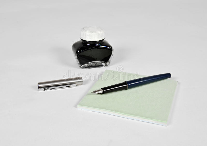Fountain pen with ink bottle and notepad. On the grey background stock images
