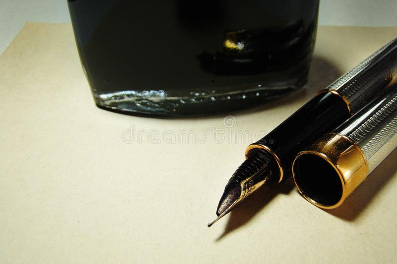 Fountain pen and ink bottle on old paper background royalty free stock photo