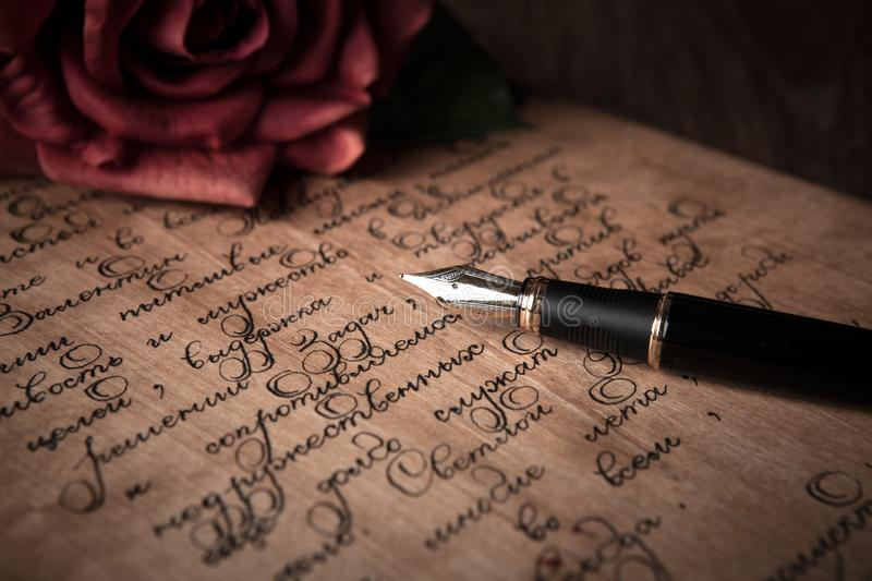 Fountain pen on letter with text and red rose stock image