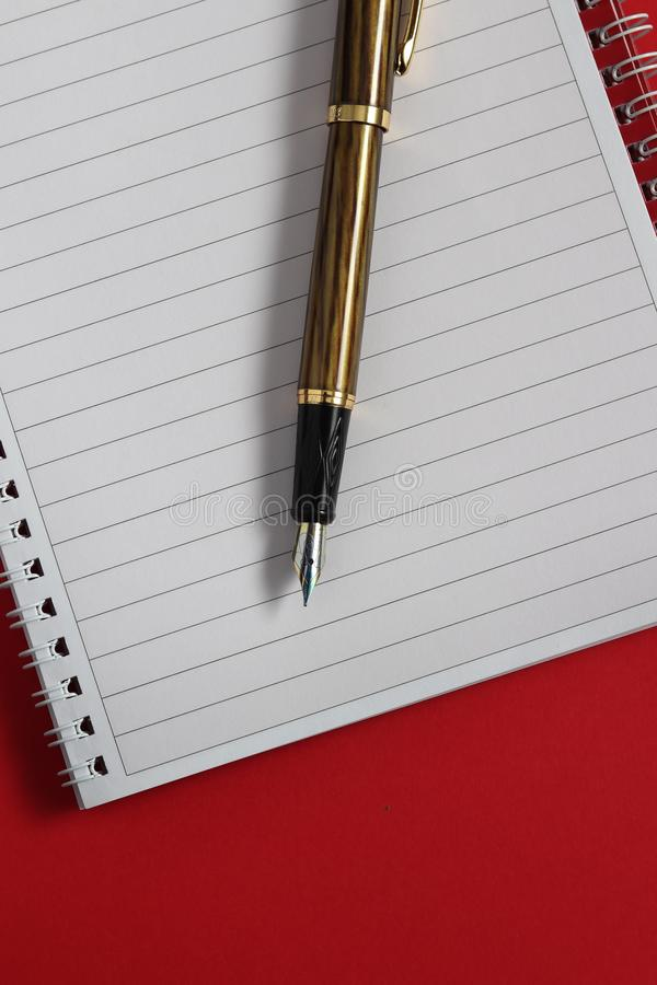 Fountain pen and notebook on table. From above stock photography