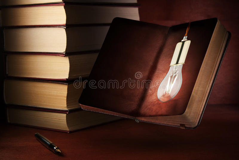 Fountain pen and open notepad on a wooden table. Concept of an idea, a light bulb in a notebook. royalty free stock photos