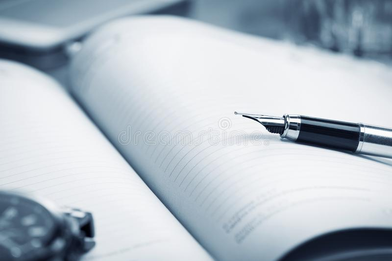 Fountain pen on paper notebook. Close-up view of fountain pen on paper notebook royalty free stock images