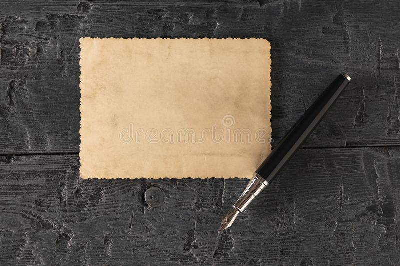 A fountain pen and a piece of antique paper on a black table. Retro writing paper. Flat lay royalty free stock photos