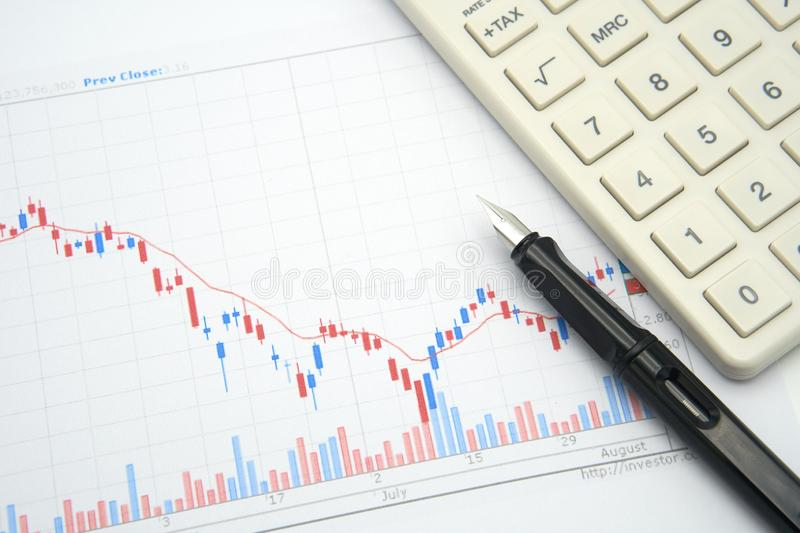 Fountain pen placed on the stock chart is the background Investment Analysis investment and white calculator using as background stock image