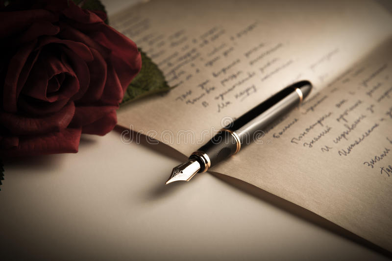 Fountain pen on text sheet paper with rose royalty free stock photos