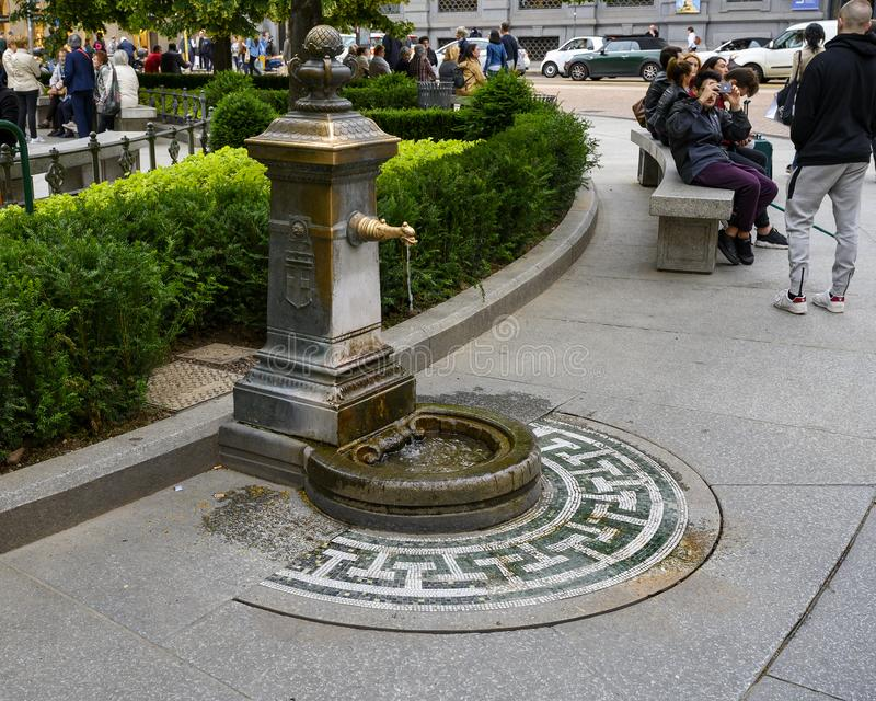 Fountain in Piazza della Scala, a pedestrian square in Milan, Italy. Pictured is a bronze water fountain in Piazza della Scala, a pedestrian square in Milan royalty free stock photo