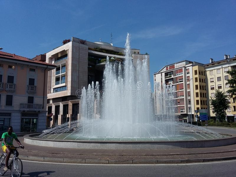 Fountain in Piazza San Lorenzo in Gallarate town in Italy. Gallarate, Varese / Italy - August 17 2018: Water jets, in the fountain shot by day in the city in stock images