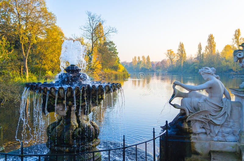 Fountain and sculpture by the Serpentine Lake at Hyde Park. Hyde Park in autumn royalty free stock photo