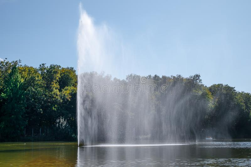 Fountain spraying water against the background of forest. And clear sky stock images