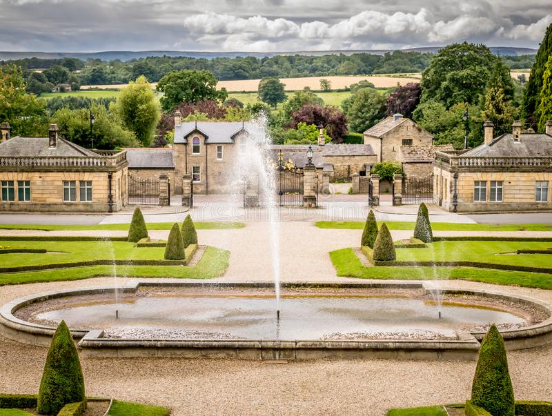 Fountains in a botanical garden, fields and clouds in the background. Fountains spraying water in a garden. a gate house and cottages. fields and a forest in the royalty free stock image