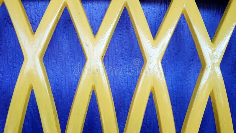 Four X abstract design yellow. With blue background from long chair plastic shiny newly painted stock photography