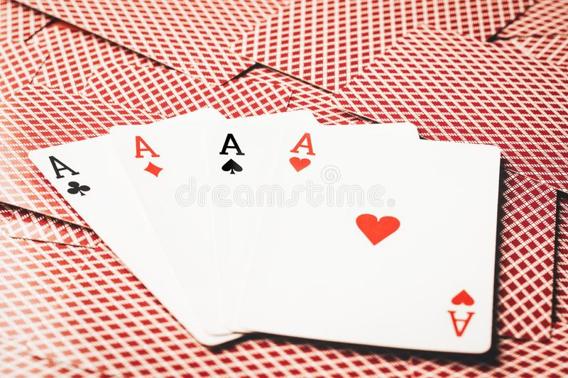Four aces of poker on the background of scattered cards unfolded back side stock images