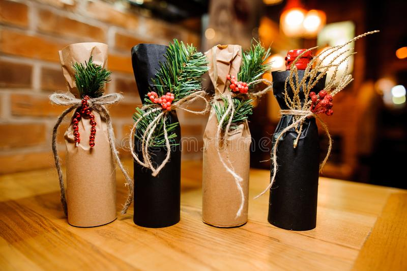 Four adorable christmas decorated bottles with ribbons and fir-tree branch stock photography