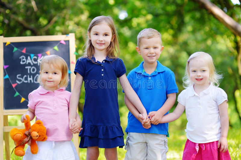 Four adorable little kids are going back to school royalty free stock photos