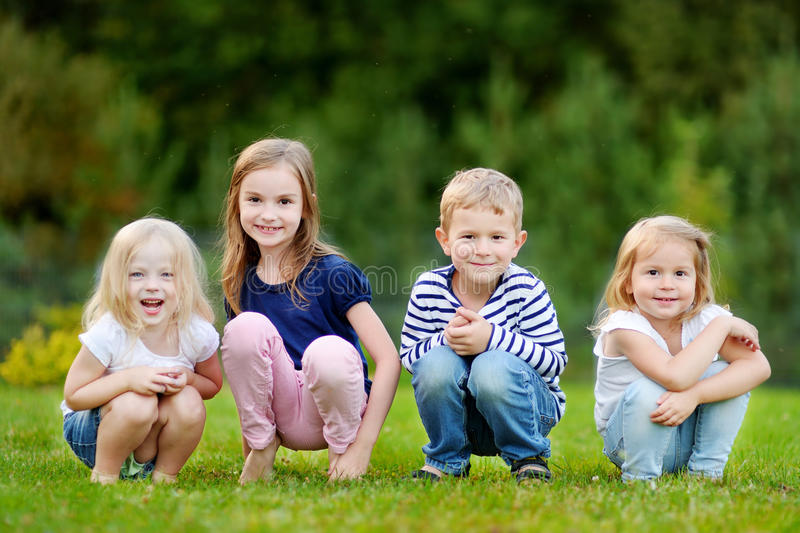 Four adorable little kids outdoors at summer day stock images