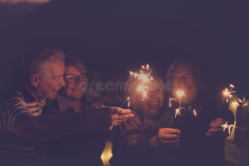 Four aged people having party by night new year 2020 celebration royalty free stock images