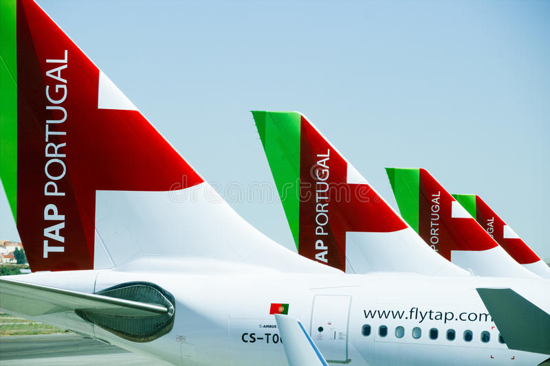 Four airplane tails with TAP Portugal logo. LISBON, PORTUGAL - JUNE 27 2015: Tails of four airplanes of the TAP Portugal airline company standing on the ground stock image