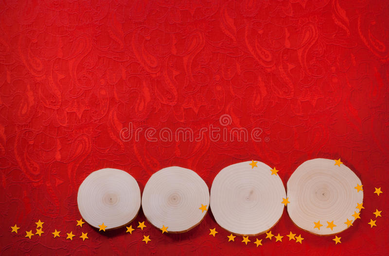 Four alder saw cuts and yellow asterisks on red ornate fabric ba. Ckground. Christmas and New Year's background stock photo