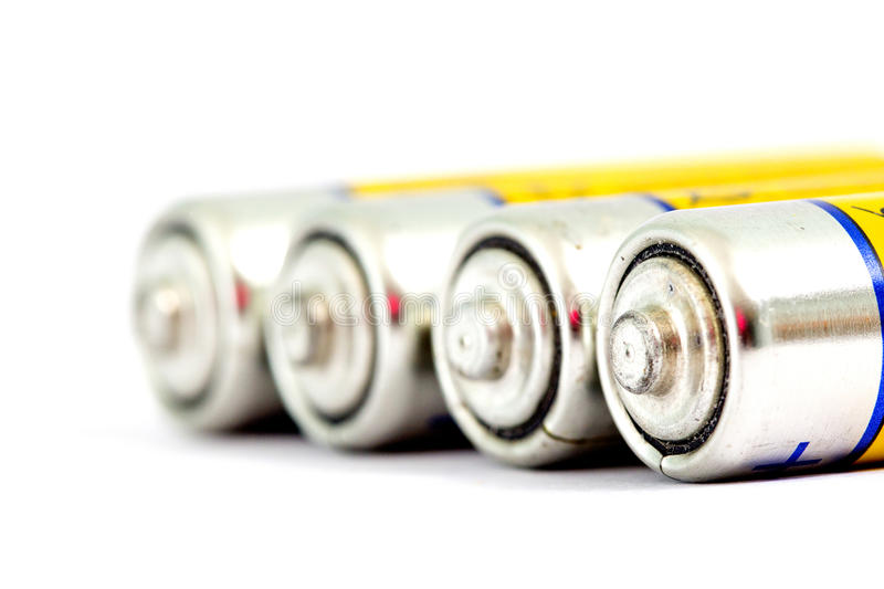 Four alkaline batteries AA size with shallow dof. Image of a four alkaline batteries AA size with shallow dof royalty free stock photos