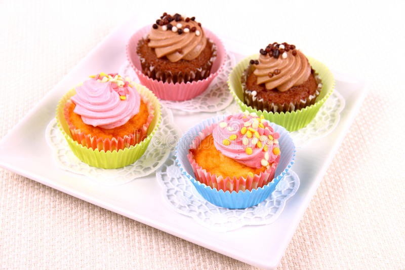 Four appetizing cupcakes on white plate. Top view stock images