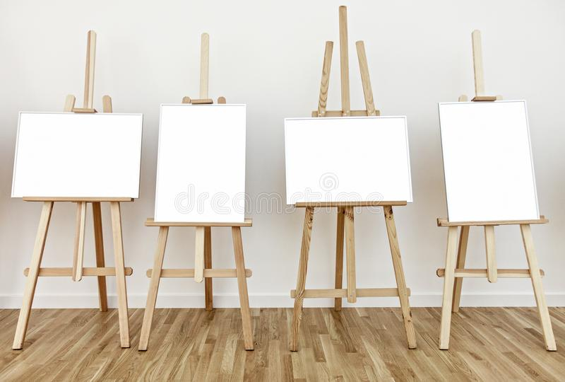Four art studio easels with blank white painting frames. Four art studio easels with blank white frames to add paintings or pictures royalty free stock photography