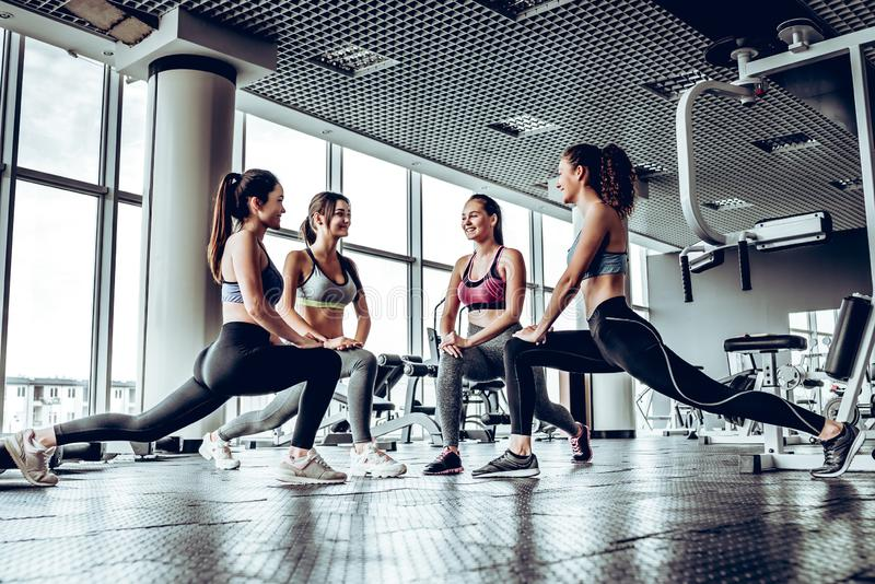 Four athletic woman performing low fallouts in gym with panoramic windows background. stock images