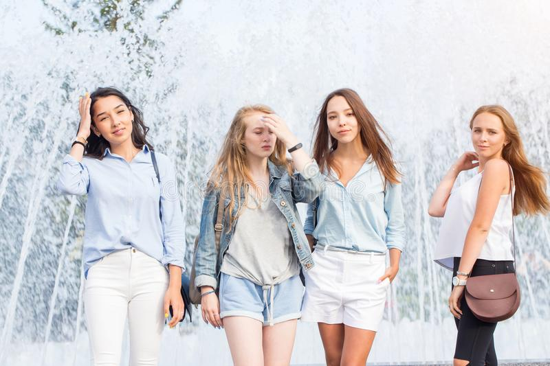 Four attractive women in summer clothes stand near the fountain on a hot day. A group of attractive women. royalty free stock photo