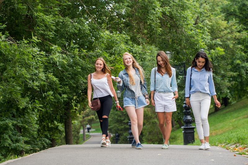 Four attractive young friends women talking and walking together on walkway royalty free stock images