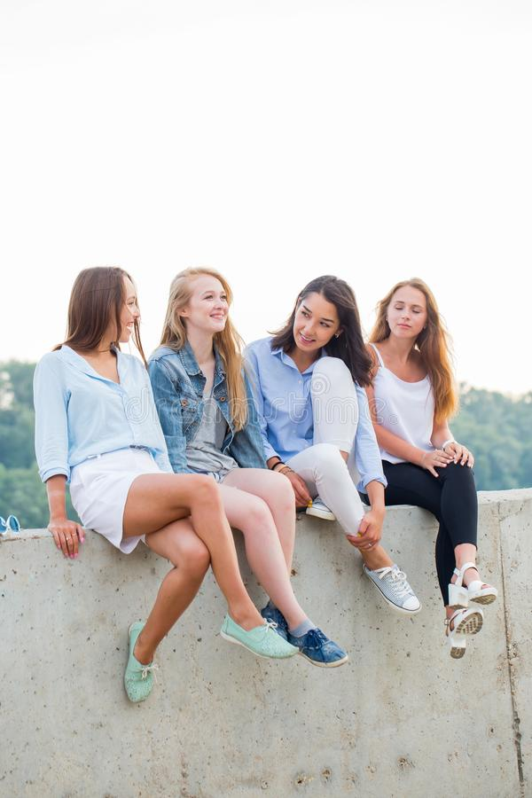 Four attractive young girls students sitting resting after school or College stock photo