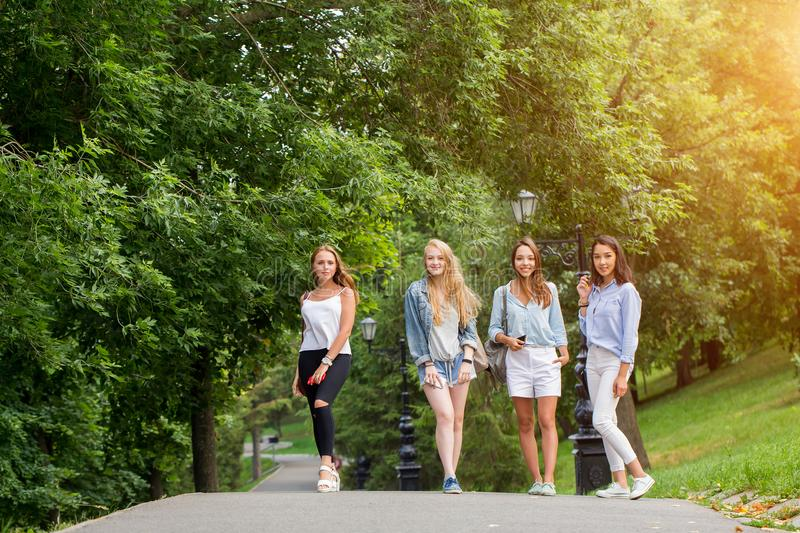 Four attractive young women talking walking together royalty free stock photos