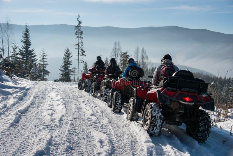 Four ATV riders on off-road quad bikes in the winter mountains. Four ATV riders on off-road quad bikes on snow in the winter mountains stock photo