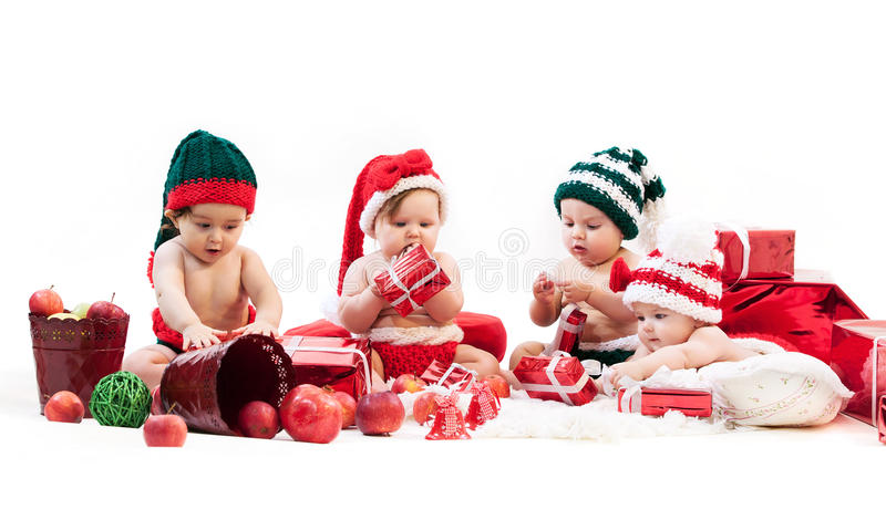 Four babies in xmas costumes playing among gifts royalty free stock photo