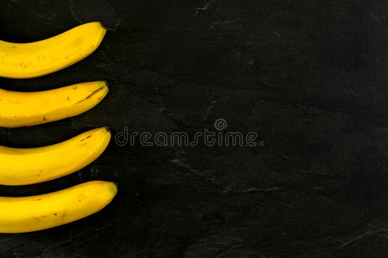 Four bananas on black slate like board photo from above, only part of them visible, more space for text right side royalty free stock image